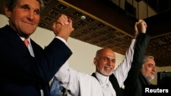 U.S. Secretary of State John Kerry (L) and Afghanistan's presidential candidates Ashraf Ghani Ahmadzai (C) and Abdullah Abdullah hold their arms in the air together after announcing a deal for the auditing of all Afghan election votes earlier this summer. (file photo)