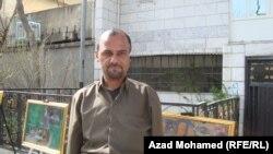الفنان اراز عثمان امام لوحات معرضه في السليمانية