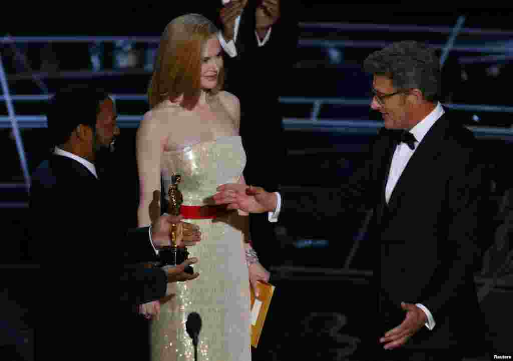 Actors Chiwetel Ejiofar and Nicole Kidman present director Pawel Pawlikowski (right) with the Oscar for best foreign language film Ida. Filmed in black and white, Ida tells the story of a novice in 1960s Poland who must decide whether to take her vows and become a nun - after learning that her family were Jews.