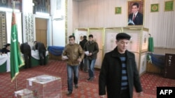 People cast their ballots in front of a portrait of President Gurbanguly Berdymukhamedov at a polling station in Ashgabat on December 15.
