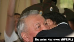 A relative bids goodbye to Zhaksylyk Doskaliev (facing camera), the former Kazakh health minister who was sentenced to seven years in prison on a corruption charge.