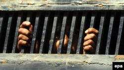 FILE: An Indian fisherman peers through prison bars while awaiting release in Karachi, Pakistan.