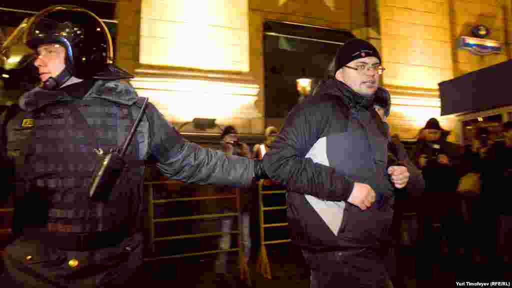 Police detain an activist during a protest rally by the opposition group Another Russia in central Moscow.
