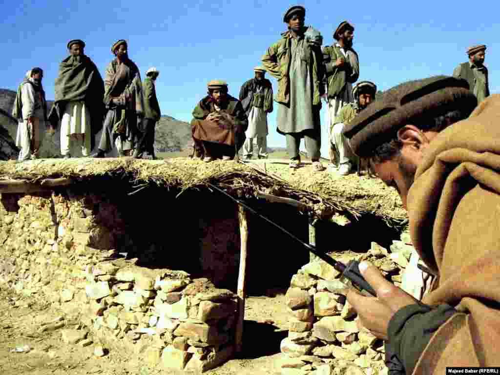 Афганскія ваяўнікі каля ўваходу ў пячоры ў гарах Тора-Бора, дзе, паводле некаторых паведамленьняў, бін Лядэн хаваўся ў сьнежні 2001