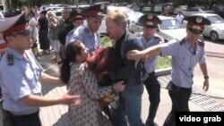 Полиция АТФ банкі алдында наразылық шарасын өткізіп жатқан азаматтардың бірін әкетіп барады. Алматы, 15 шілде 2014 жыл. (Көрнекі сурет)