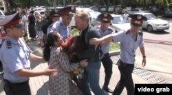 Полиция АТФ банкі алдында наразылық шарасын өткізген азаматтардың бірін ұстап әкетіп барады. Алматы, 15 шілде 2014 жыл. (Көрнекі сурет)