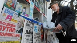 A man looks through a newspaper at a kiosk with Russian newspapers displayed outside in the Crimean port of Sevastopol on March 27.