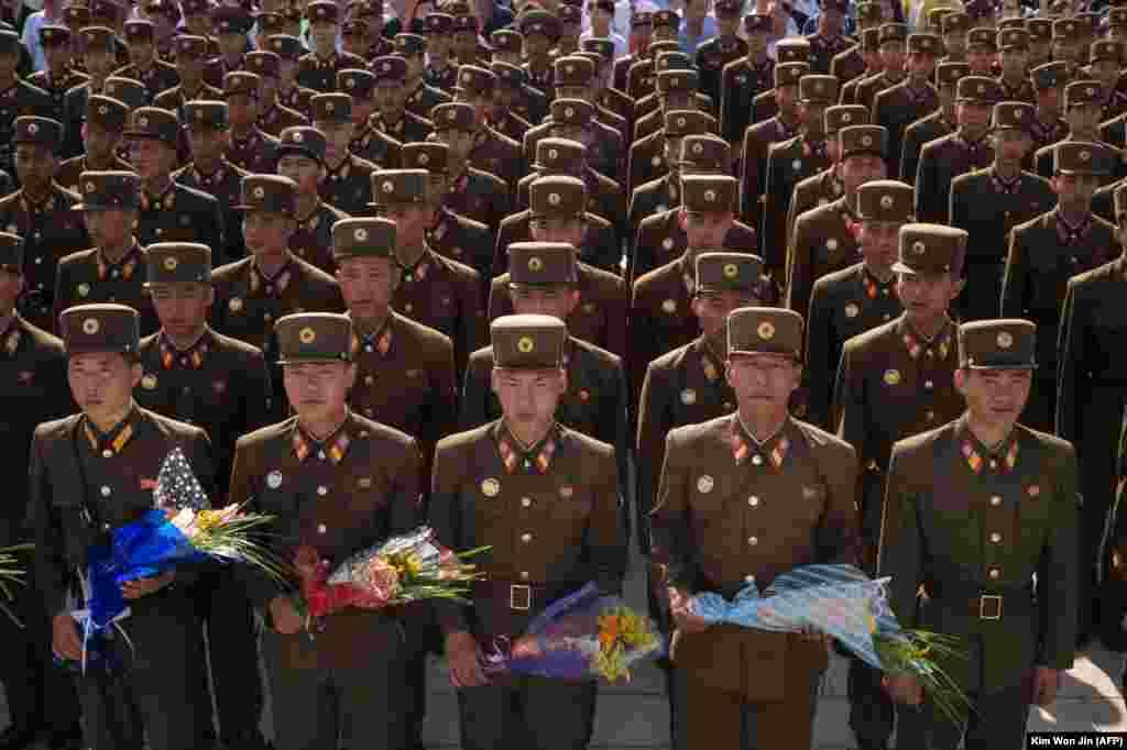 Түндүк Кореянын аскерлери Ким Ир Сендин каза болгонунун 25 жылдыгын белгилөө учурунда өлкөнүн мурдагы лидерлери Ким Чен Ир менен Ким Ир Сендин эстелигине гүл коюш үчүн күтүп турушат.