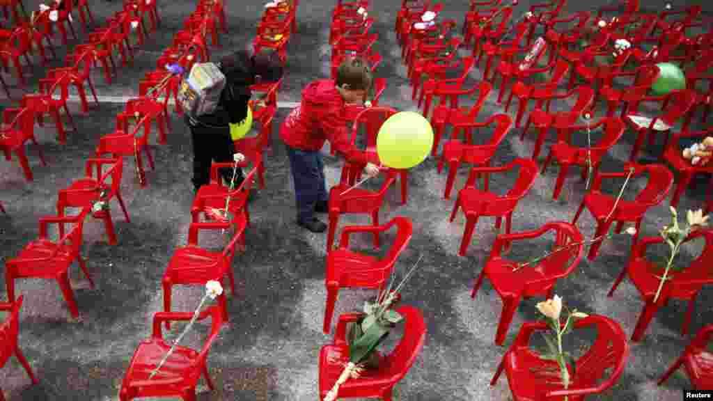 Дети кладут цветы и крепят шары к маленьким стульям, символизирующим детей, погибших в годы осады Сараево. Инсталляция 11 541 стула разной велечины (по количеству людей, погибших в боснийской столице) была приурочена к 20-й годовщине начала войны в Боснии 6 апреля. (Reuters/Дадо Рувич)