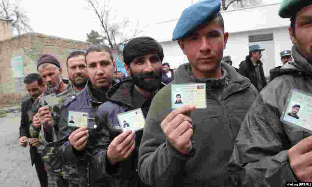 Afghan men wait for to enter a polling center and cast their votes in presidential and provincial-council elections in Kabul on April 5.