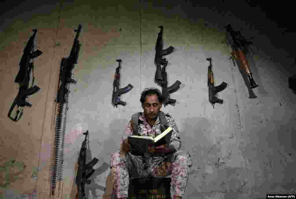 Сырыйскі паўстанец чытае Каран на пазыцыі на прадмесьці Алепа.
