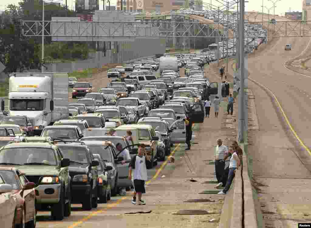 Drivers and passengers wait outside their vehicles during a massive traffic jam as travelers try to leave downtown New Orleans on August 28. Authorities had ordered hundreds of thousands of residents to leave vulnerable areas before the hurricane hit. Many were unable to do so.