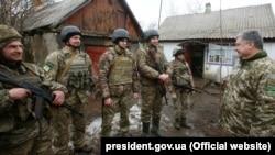 Президент України Петро Порошенко спілкується з військовими в Луганській області, 16 березня 2018 року. Він відвідав визволений від російських гібридних сил населений пункт Катеринівка, а також місто Золоте в Луганській області