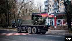 A military truck carries what appears to be an antiaircraft gun through the streets of Donetsk on November 2.