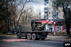 A military truck carries an antiaircraft gun through the streets of Donetsk on November 2.