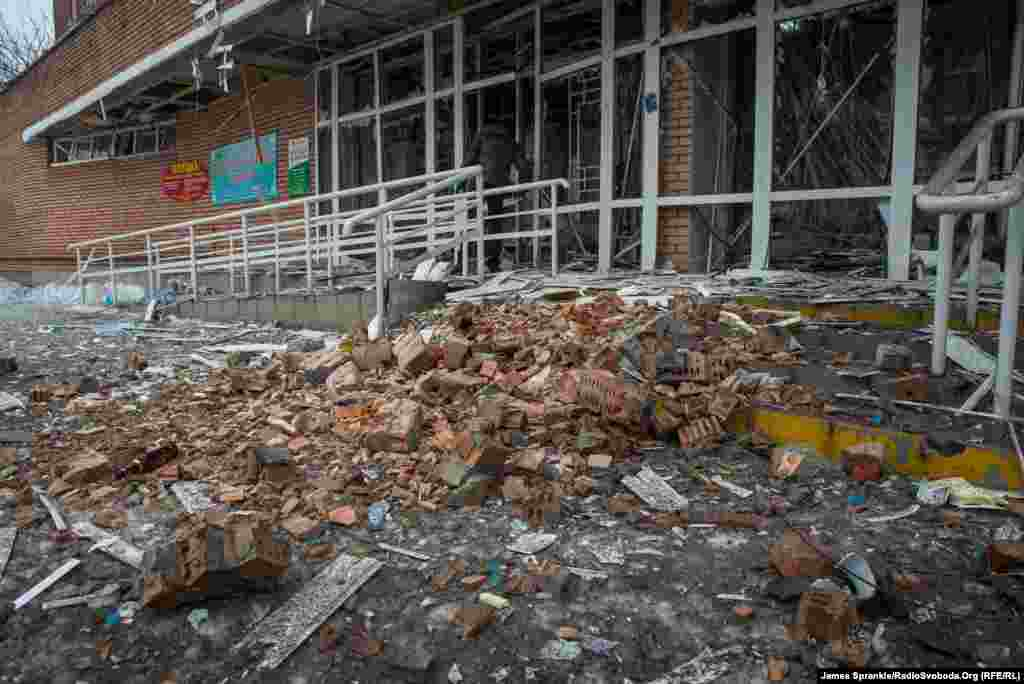 The entrance to the hospital, including a ramp for prams and wheelchairs, covered in rubble.