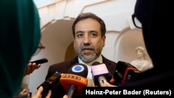 Iran's top nuclear negotiator Abbas Araqchi talks to journalists after meeting senior officials from the United States, Russia, China, Britain, Germany and France in Vienna, October 19, 2015