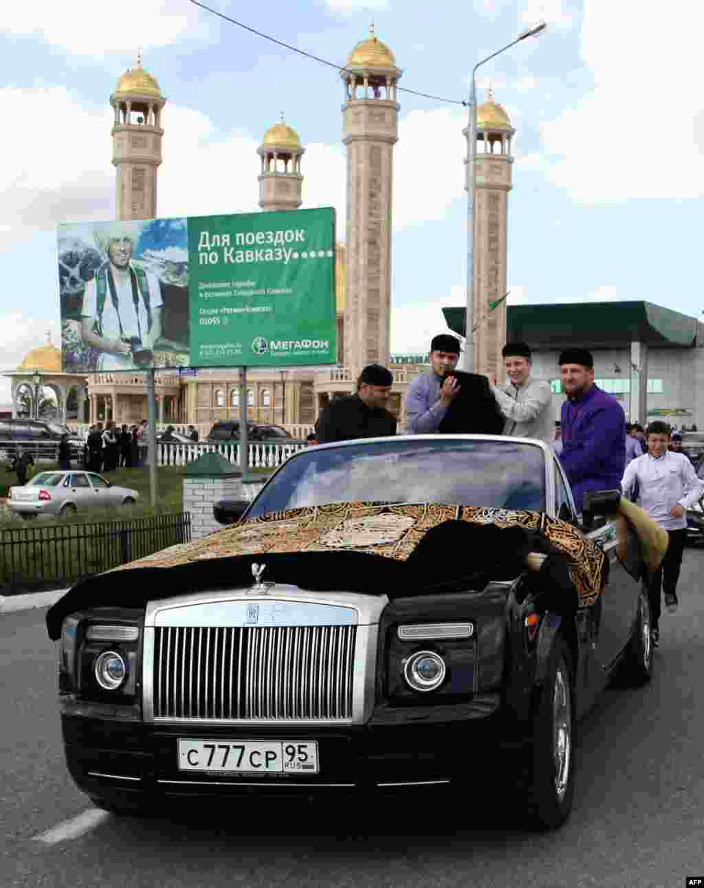 Kadyrov (right) rides in a Rolls-Royce Cabriolet in Grozny in 2011.