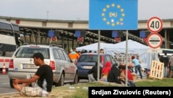 Migrants gather near a European Union sign at the Croatia-Slovenia border crossing at Bregana, Croatia, on September 19.