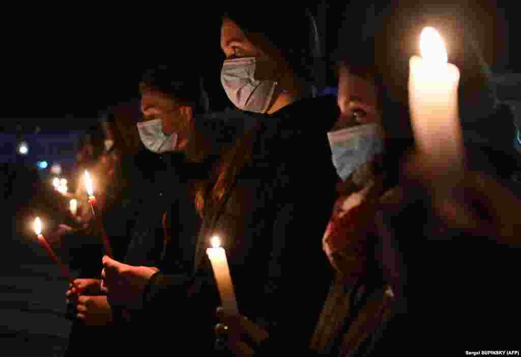 Oameni și lumânări la memorialul dinSlavutîci.