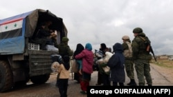 SYRIA -- A Russian soldier passes out food aid to Syrian civilians as they cross from rebel-held areas in Idlib province into regime-held territories on December 27, 2018, through the Abu Duhur crossing.