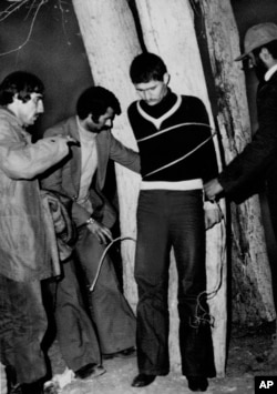 An Iranian military police sergeant is tied to a tree for execution by a revolutionary committee firing squad in Qazvin, Iran, March 3, 1979.