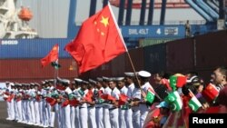 Chinese families along with Pakistani Navy servicemen wave flags to welcome a Chinese naval vessel upon its arrival to participate in an exercise in Karachi in February.