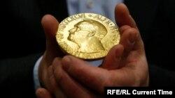 Një person mban në duar një medalje të Çmimit Nobel. Fotografi nga arkivi.