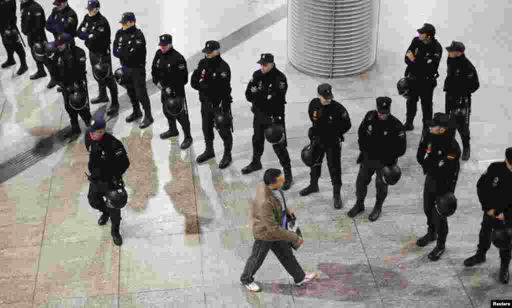 A passenger passes a line of police at Atocha rail station during a 24-hour nationwide general strike in Madrid. Spanish and Portuguese workers staged the first coordinated strike across the Iberian peninsula on November 14, shutting down transport, grounding flights, and closing schools to protest austerity measures and tax hikes. (Reuters/Paul Hanna)
