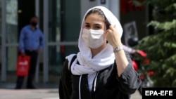 IRAN PANDEMIC CORONAVIRUS COVID19 -- Iranians wearing face masks walk past in a street of Tehran, Iran, 04 August 2020.