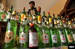 Pakistani Police officials display a huge quantity of smuggled liquor which was recovered during an operation in Pakistan.