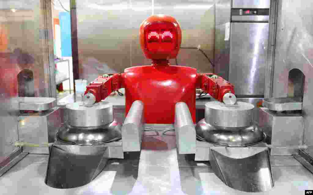 A robot cooks in a robot-themed restaurant in Harbin in northeast China's Heilongjiang Province. Twenty robots perform a variety of chores, from ushering in guests to waiting tables and cooking dishes. (AFP)