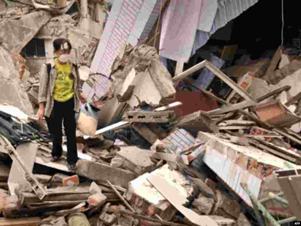 China -- An injured resident walks through the debris of her destroyed house in the town of Beichuan, Sichuan provinc, 15May2008