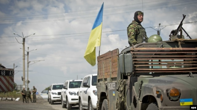 A Ukrainian soldier watches from an armored vehicle with a Ukrainian flag in front of OSCE vehicles at a checkpoint in the village of Debaltseve, in eastern Ukraine, on July 31.
