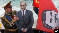 Русин облечен како царот Николај Втори поставува слика од Путин и знаме со ликот на рускиот диктатор Сталин на Црвениот плоштад во Москва