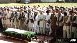 Mourners pray near the body of Amanullah Aman, head of the Independent Election Commission (IEC) in Konduz, on September 19, after he was killed by the Taliban.