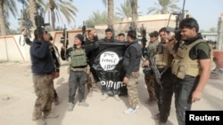Iraqi security forces pose with an Islamic State flag that they pulled down in the city of Ramadi in January.