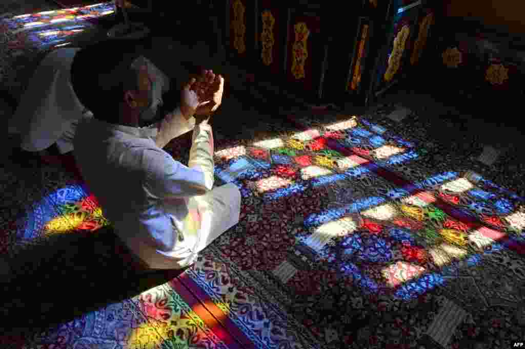 После молитвы верующие собираются за праздничными столами, на которых важное место занимают сладости На фото - мужчина молится в Кашмире во время Рамазана