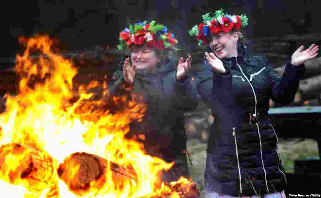 """Women wearing floral wreaths take part in a """"Grandfather Frost"""" celebration in Belarus. (TASS/Viktor Drachev)"""