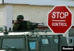 Вооруженный человек без опознавательных знаков на КПП у военной базы в Привальном близ Симферополя. 13 марта 2014 года.