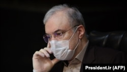 Iranian Health Minister Saeed Namaki wears a protective mask during a cabinet session in the capital Tehran, March 25, 2020