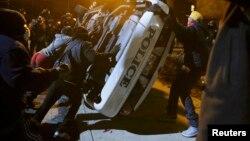 Демонстранттар полиция унаасын оодарууда. Фергюсон, 25-ноябрь, 2014-жыл.