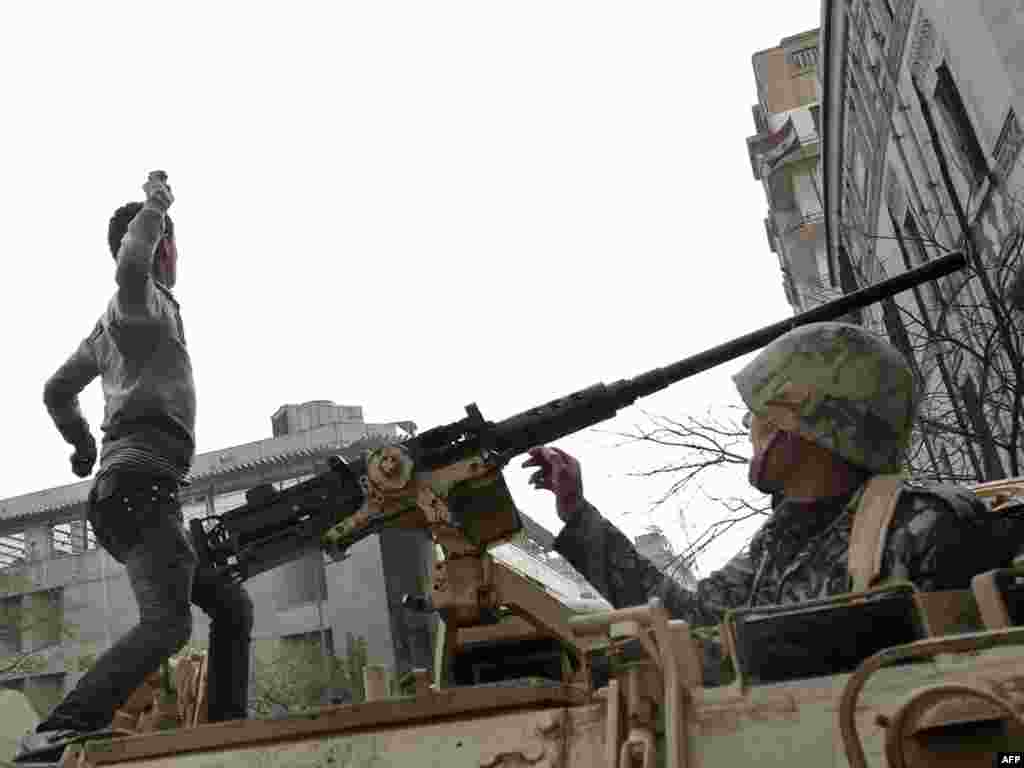 A demonstrator throws a stone from atop an armored vehicle in central Cairo on January 29.
