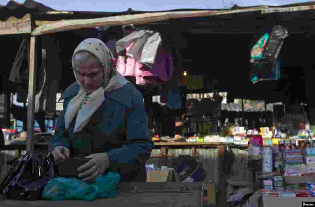 A woman counts money at a market in the town of Tkvarcheli.