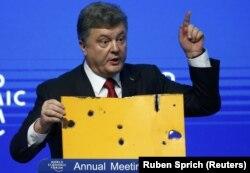Президент України Петро Порошенко демонструє фрагмент пасажирського автобуса, який був знищений ракетним ударом російсько-сепаратистських сил на околиці Волновахи 13 січня 2015 року. Давос 21 січня 2015 року