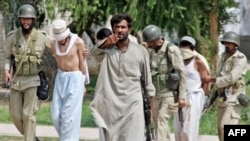 Pakistani Army soldiers escort blindfolded, detained militants who were holed up in the Red Mosque in Islamabad on July 5, 2007.