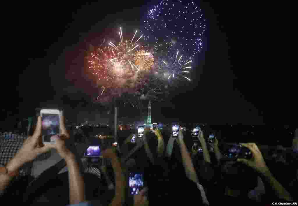People use their mobile phones to capture the fireworks show near the Minar-e Pakistan, or Pakistan monument, during celebrations in Lahore early on August 14.