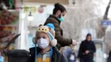 IRAN -- An Iranian child wearing face mask walks on a street of Tehran, February 26, 2020