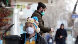 IRAN -- An Iranian child wearing face mask walks on a street of Tehran, February 26, 2020