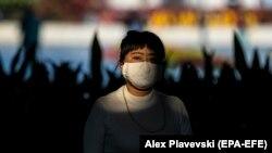 شهروند چینی در گوانگجو در چین، ماسک بر صورت زده است